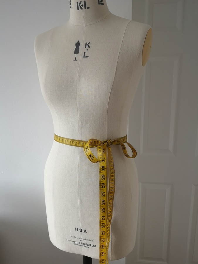 A plain mannequin with a measuring tape tied around it in a knot