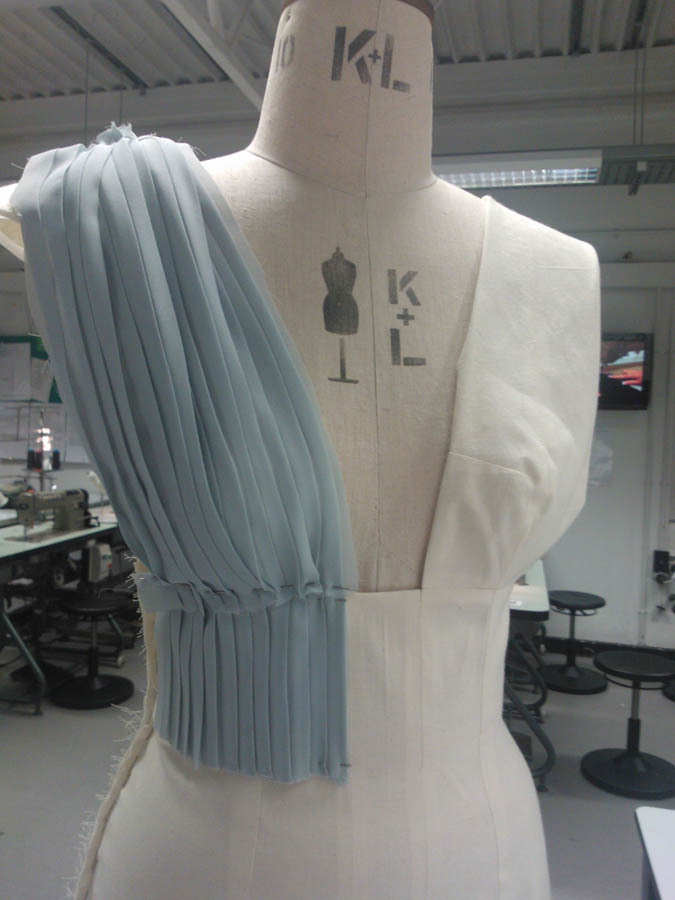 A mock up version of a pleated dress on the mannequin to show a stage in the design process